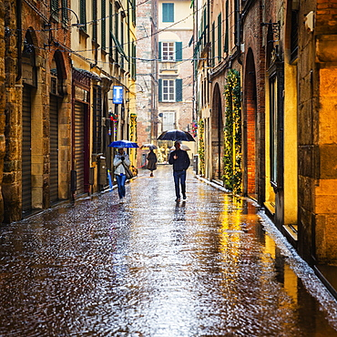 People walking the wet city streets in Lucca, a city and commune in Tuscany, Central Italy, on the Serchio, a fertile plain near the Tyrrhenian Sea. It is the capital of the Province of Lucca. It is famous for its intact Renaissance-era city walls.