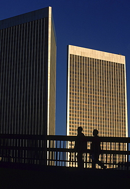 At sunset, pedestrians walk past the skyscrapers in Century City, CA.