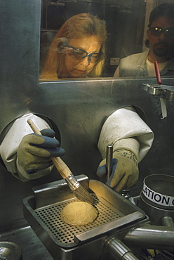 Plutonium button Plutonium metal button at Rocky Flats, CO. It consists on 98 percent plutonium and the rest other metals. Terri Coleman is the process specialist who is holding the button and using a brush to clean off oxide.