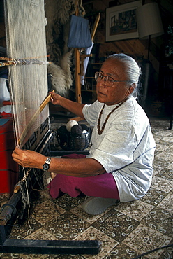 A Navajo weaver weaves a rug in her home near Shiprock, New Mexico on the Navajo Indian Reservation.