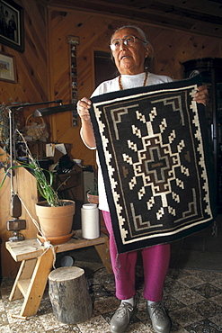 A Navajo weaver holds a rug in her home near Shiprock, New Mexico on the Navajo Indian Reservation.