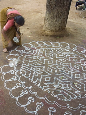 A woman performs the morning ritual of making a Rangoli, a Hindu religious decoration, outside her home in Hampi, Karnataka, India.