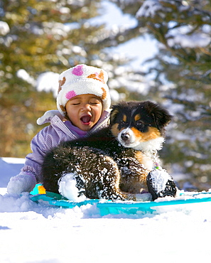1-year-old baby girl sledding with her dog, a 12-week-old puppy, in Carbondale, Colorado.