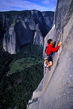 Chris McNamara uses a sky hook to move higher while rock climbing Mescalito on El Capitan in Yosemite National Park, California. By the time McNamara was 18 years old he had rock climbed the 3000 foot high El Capitan more than 50 times. El Capitan is considered a big wall and usually requires aid climbing.