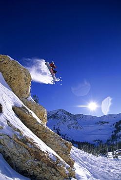 Dan Gavere jumping off a cliff on his snowboard at Snowbird, Utah.