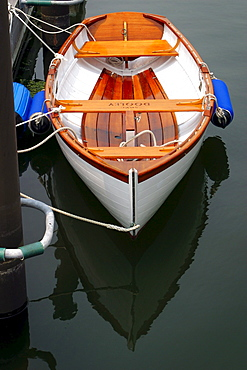 A row boat is tied to a dock.