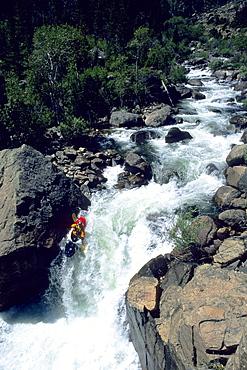 A whitwwater kayaker negotiates a Class V waterfall on the Popo Agie River, Lander, Wyoming. (Photo by Greg Von Doersten, Aurora)