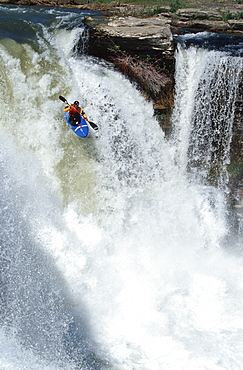 Young man (Scott Feindel) kayaking over Lumbreck Falls near Pincher Creek, southern Alberta, Canada.