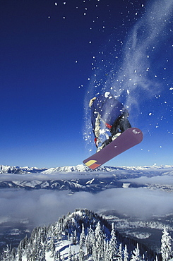 Young male snowboarder (Steve Whelan) in the air over cloud-shrouded valley at Fernie Alpine Resort, Fernie, British Columbia, Canada.