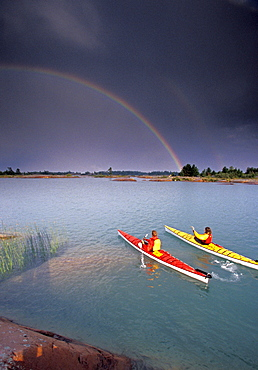 Young couple sea-kayaking through archepelago of granite islands of Canadian Shield in Georgian Bay, Lake Huron near Philippe Edward Island, Ontario, Canada. A passing thunder storm results in a double rainbow.