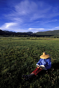 Nina Schmalenberger reads a book while camping in Hope Valley near Lake Tahoe, California, in the Sierra Nevada Mountains. She is wearing a straw hat.