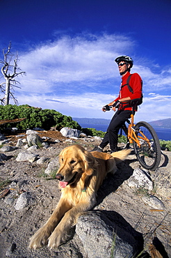 Dan Moses takes a break from mountain biking with his dog Mac and admires the view over Emerald Bay in Lake Tahoe, California.
