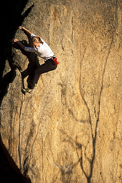 Beth Rodden holds onto the prow of a boulder with aspen shadows visible on its face outside Estes Park, Colorado. Beth Rodden is one of the worlds leading climbers.