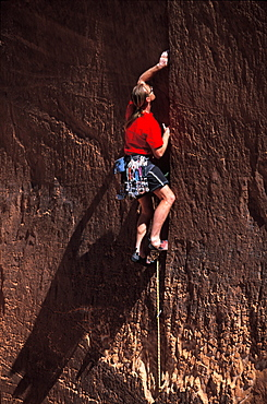 Tim Burnett looking to place a cam somewhere in the crack he is climbing in Lake Powell, Utah.