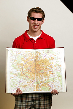 White male college student holding world map.
