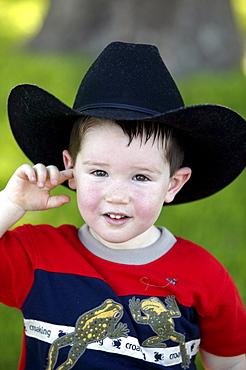 A little boy wears a black cowboy hat.