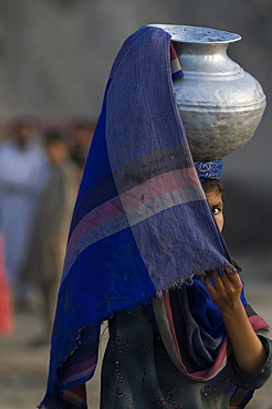 An adolescent Pashtun girl shields her face as she carries water  through the streets of the Meira camp for earthquake survivors, Northwest Frontier Province, Pakistan.  The conservative code of the Pashtun tribe of the area dictate that girls must cover themselves, including their faces, after their first period.  The crowded life in the camp has made such rules difficult to follow. The Meira Tent camp (also called Mera, or Maria camp), is located on the Indus River in the Battagram district.  The camp, the largest for displaced people in Pakistan, hosts over 21,000 earthquake survivors, primarily from the Allai valley in Pakistan's NWFP, one of the areas worst-hit by the October 8, 2005 earthquake.