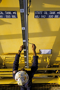 A oil drilling worker holds a large wrench and tightens a knob.