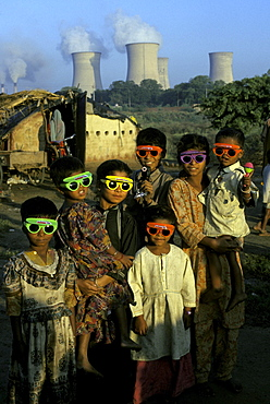 A group of young children gather outside their humble dwellings in India with a Nuclear Plant Facility in the background.