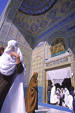 Women in burqas flock like doves to the entrance of the main mosque at the Blue Mosque complex, Mazar-i-Sharif, Balkh Province, September 23, 2002.  Wednesday mornings are reserved for women to come and worship at the mosque.Elaborate tilework and decorated spires adorn the mosque, also known as the Shrine of Hazrat Ali (Hazrat Ali was the son-in-law of the prophet Mohammed), who is believed to be buried here.  The shrine, of particular importance for Afghanistan's Shi'ite Muslims, was first built in the 12th century, destroyed by Genghis Khan, and rebuilt in 1481.  The current mosque, considered by some to be one of the most beautiful in Central Asia, is a modern restoration.