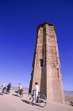 Men and boys on bikes ride past a towering, ancient  minaret, outside of Ghazni, Afghanistan, October 1, 2002. Made of brick decorated with Kufic and Naksh Script and floral motifs, the  minaret dates back to  the early 12th century and was built by Sultan Masud III of the Ghaznavid Dynasty, who ruled over an empire encompassing much of Afghanistan, Northern India, Persia and Central Asia. The minaret was once three times as tall as its current 70 feet, and is thought to have been part of a large mosque complex. Now an  important truck stop on the road to Kandahar, Ghazni, located on the Lora River at the elevation of 2,225 meters, is the capital of Ghazni province   and is a  market for sheep, wool, camel hair cloth, corn, and fruit-it also continues to be a haven for  Taliban insurgents.