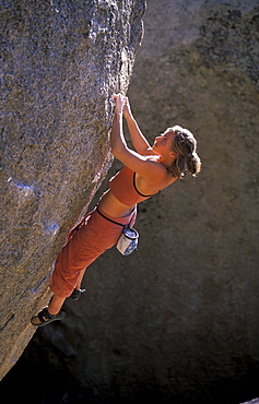 Rock climber Kelly Doyle climbing an overhanging bouldering route in the Buttermilks, outside of Bishop, California in the Sierra Nevada mountains near Hwy 395.