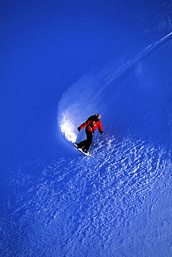Professional snowboarder Barrett Christy snowboarding in the backcountry on a bluebird powder day, Mt Baker, Washington.