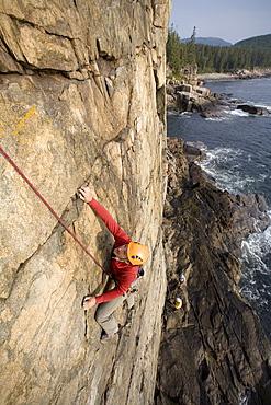 A man rock climbing on oceanside cliffs in Acadia Nation Park.