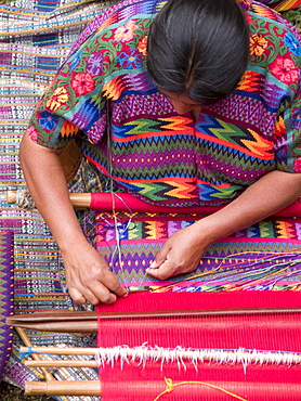 A woman from an indigenous community in Guatemala weaving while wearing an indigenous dress at work in Antigua, Guatemala.