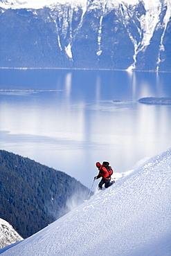 Telemark skier descends steep mountain in backcountry of southeast Alaska.