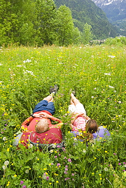 Two hikers rest in a field of flowers in the countryside near Chamonix, France.