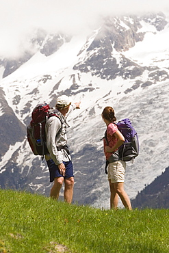 Two people hike by Mont Blanc near Les Houches, France.
