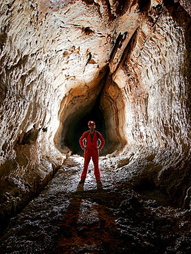 A cave explorer poses in a tube in a cave in Mulu National Park