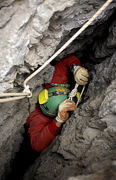 Cave explorer struggles to negotiate a tight squeeze in the entrance of a cave in the White Mountains on the island of Crete.