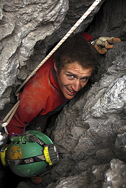 A cave explorer has to remove his helmet in order to pass the tight squeeze in an entrance to a cave in the White Mountains on t
