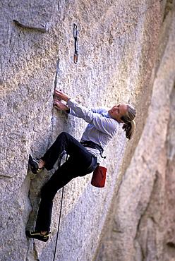 A woman lead climbing The Optimist in Smith Rock, Oregon.