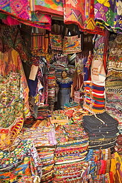 A local vendor sells her wares of authentic and colorful textiles in shopping both, Antigua, Guatemala