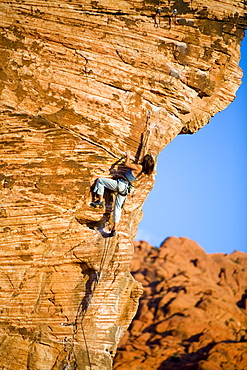 A women stretches to clip the draw on the crux while climbing.