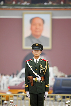 Soldier on guard on Tiananmen Square in Beijing in front of the Forbidden City and the big portrait of Mao Zedong