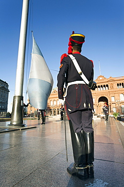 A soldier stands in front of the argentine flag during an everyday ceremony in front of the pink house (presidencial building) in Buenos Aires, Argentina.