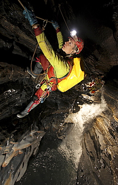 A young man holds onto a rope above a river in a cave in China.