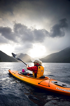 Middle aged woman kayaking on Lake Crescent, Olympic National Park, WA, USA