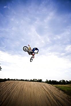 Rear-view of a motocross biker about to land a stunt in Brainerd, Minnesota.