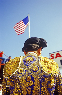 Matador stands underneath the American flag before the start of a bullfight.
