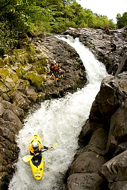 Overhead view of a kayaker going down a narrow and steep rapid with other kayakers watching.
