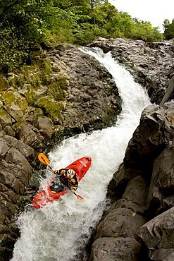 Overhead view of a kayaker going down a narrow and steep rapid.