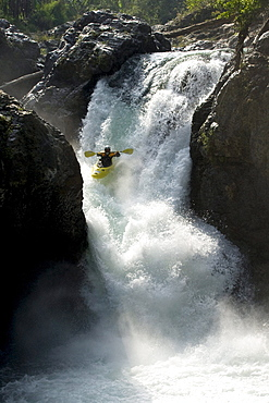 Young kayaker dropping into a large rapid / waterfall in the jungle in Mexico.