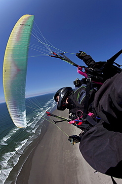 Foot perspective of a man paragliding and turning high above a beach.