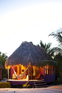 A woman sits in a hammock on the porch of her thatch cabana at a luxury hotel in Belize.