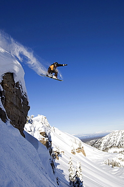 A male snowboarder jumps off a cliff in the Wyoming Backountry.